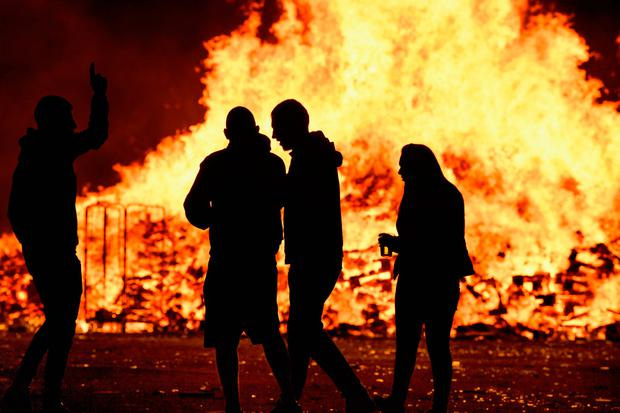 Loyalist are silhouetted as they gather in front of the bonfire on the Sandy Row area on July 12, 2017 in Belfast, Northern Ireland. (Photo by Jeff J Mitchell/Getty Images)
