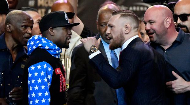 Floyd Mayweather Jr. (L) faces off for the first time with UFC fighter Conor McGregor during a press call at the Staples Center in Los Angeles, California on July 11, 2017. The two will fight August 26th in Las Vegas, Nevada. / AFP PHOTO / Gene Blevins