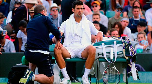 Novak Djokovic receives treatment during his match against Tomas Berdych on day Nine of the Wimbledon Championships at The All England Lawn Tennis and Croquet Club, Wimbledon.