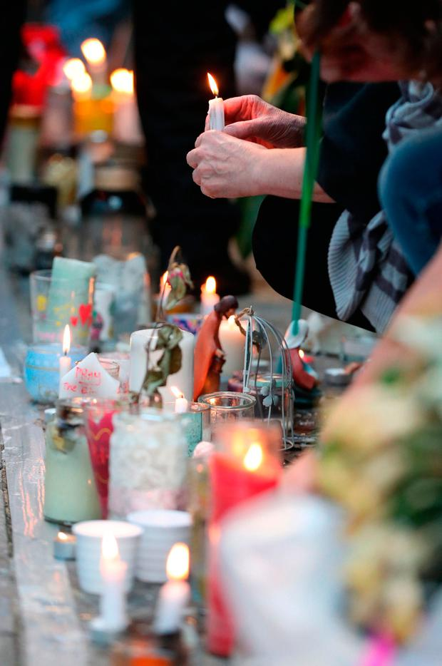 People place candles at the memorial wall on Bramley Road, London, as they attend a vigil to mark four weeks since the Grenfell Tower fire Credit: Jonathan Brady/PA Wire