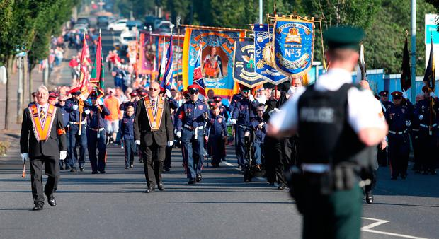 Orange Order members march past the Ardoyne shops on the Crumlin Road in Belfast as part of the 'Twelfth of July' celebrations. Photo: Niall Carson/PA