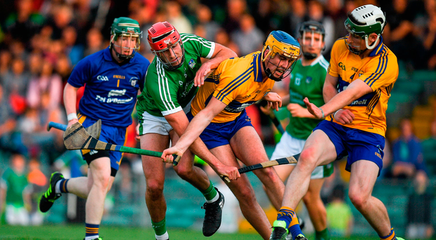Barry Nash of Limerick in action against Dara Walsh and Conor O'Halloran, right, of Clare. Photo by Brendan Moran/Sportsfile