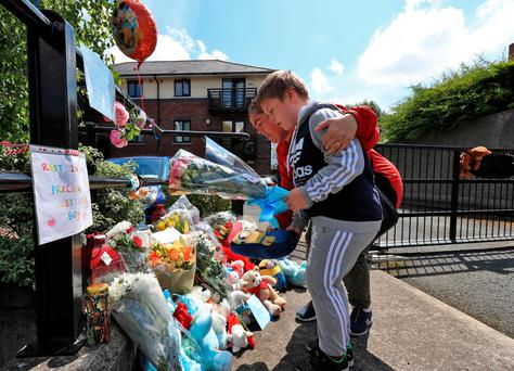Neighbour Michael Fitzgerald Hayden (8) and his mother Jane place flowers at the entrance to the Riverside Apartments, Kimmage. Photo: Colin Keegan/ Collins