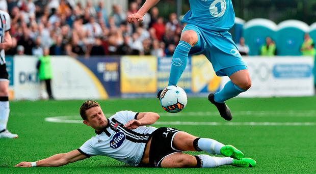 Dane Massey slides in to challenge Pal Andre Helland of Rosenborg at Oriel Park. Photo by David Maher/Sportsfile