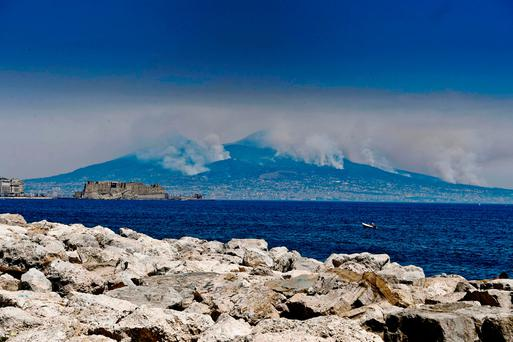 Smoke rises from wild fires burning on the slopes of Mt. Vesuvius volcano as the Castel dell'Ovo castle in seen in the foreground, in Naples, Italy, Wednesday, July 12, 2017. Firefighters are battling wildfires throughout southern Italy, including along the slopes of the volcano Mount Vesuvius near Naples. (Ciro Fusco/ANSA via AP)