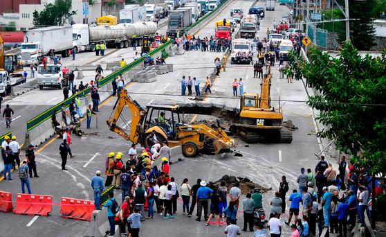 Rescue workers use heavy equipment to rescue a vehicle that drove into a sinkhole that opened up on a highway in Cuernavaca, Mexico