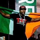 Floyd Mayweather, left, taunts Conor McGregor by wearing the Irish flag during a promotional stop in Toronto on Wednesday