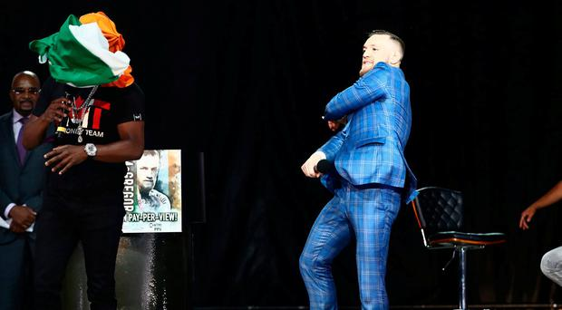 Conor McGregor throws an Irish flag at Floyd Mayweather as he speaks during a world tour press conference to promote the upcoming Mayweather vs McGregor boxing fight at Budweiser Stage. Credit: Tom Szczerbowski-USA TODAY Sports