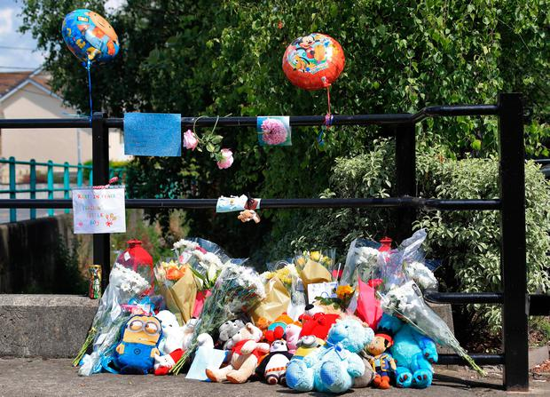 Flowers and teddy bears are left by the gates of the Riverside apartment complex in Kimmage, Dublin, where three-year-old Omar Omran was found dead. Photo: Collins