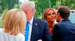 US President Donald Trump holds Brigitte Macron's hand as President Emmanuel Macron kisses Melania Trump. Photo: Getty Images