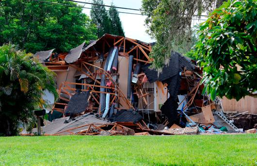 Debris is strewn about from a partially collapsed home in Land O' Lakes, Fla. (Alessandra da Pra/Tampa Bay Times via AP)