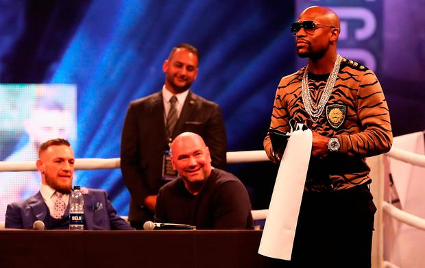 LONDON, ENGLAND - JULY 14: Floyd Mayweather Jr. takes down'Conor McGregor's name off the ring, as Conor McGregor looks on during the Floyd Mayweather Jr. v Conor McGregor World Press Tour at SSE Arena on July 14, 2017 in London, England. (Photo by Matthew Lewis/Getty Images)