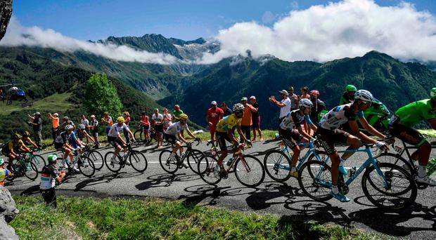 The yellow jersey group rides past fans during yesterday's short and sharp 101km Stage 13 of the Tour de France from Saint-Girons and Foix. Photo: Getty Images