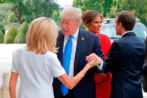 Donald Trump is greeted by Brigitte Macron in Paris Photo: MICHEL EULER/AFP/Getty Images