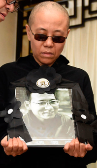 State control: Liu Xia, wife of Liu Xiaobo, holds a portrait of her husband in a photo provided by the Shenyang Municipal Information Office