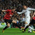 MADRID, SPAIN - FEBRUARY 13: Cristiano Ronaldo of Real Madrid is put under pressure by Jonny Evans and Phil Jones of Manchester United during the UEFA Champions League Round of 16 first leg match between Real Madrid and Manchester United at Estadio Santiago Bernabeu on February 13, 2013 in Madrid, Spain. (Photo by Gonzalo Arroyo Moreno/Getty Images)
