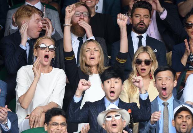 Uma Thurman (L) and Sienna Miller (R) react as they attend day 13 of Wimbledon