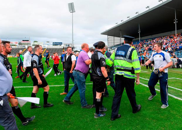 Referee Paddy Neilan is escorted off the pitch by Gardai and stadium officials. Photo: Ray McManus/Sportsfile
