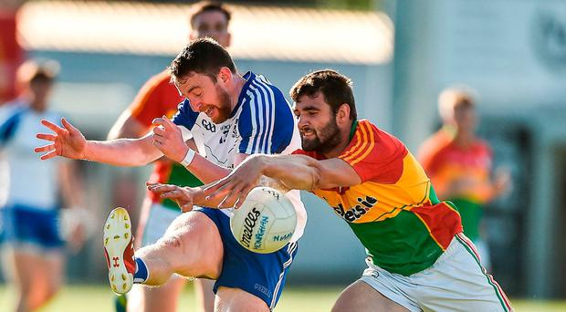 Carlow's Sean Murphy gets a great block in on Owen Duffy of Monaghan. Photo: David Maher/Sportsfile