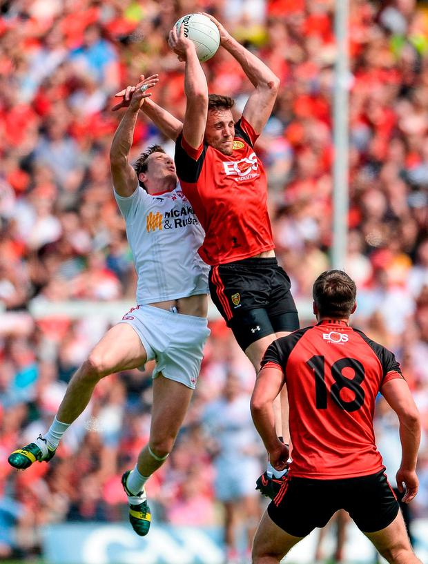 Down's Niall Donnelly wins the high ball ahead of Tyrone's Colm Cavanagh. Photo: Oliver McVeigh/Sportsfile