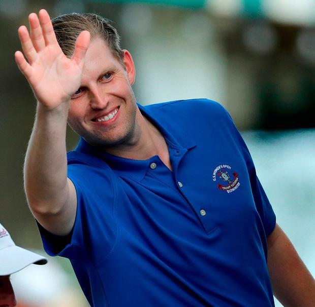 Eric Trump waves as he heads into his father's presidential suite at the club