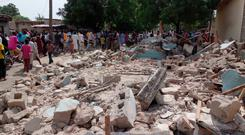 People gather at the site of a suicide bomb attack in Maiduguri, Nigeria, Monday, July 17, 2017. (AP Photo/Jossy Ola)