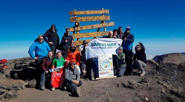 The delighted group at the summit of Mount Kilimanjaro with the washing machine