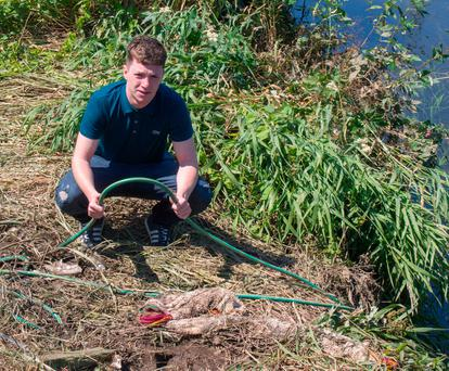 Rescue hero Andrew Johnston with the garden hose which was used in the rescue Picture: North West Newspix