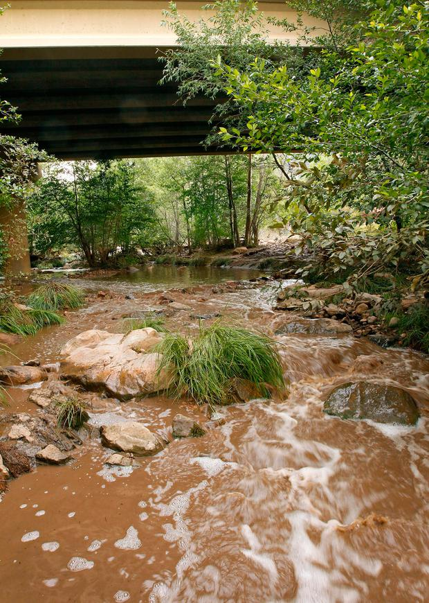 Muddy floodwaters of the East Verde River flow under a bridge where at least one victim of a flash flood was found during a search and rescue operation by the Gila County Sheriff's Office on Sunday, July 16, 2017, in Payson, Ariz. (AP Photo/Ralph Freso)