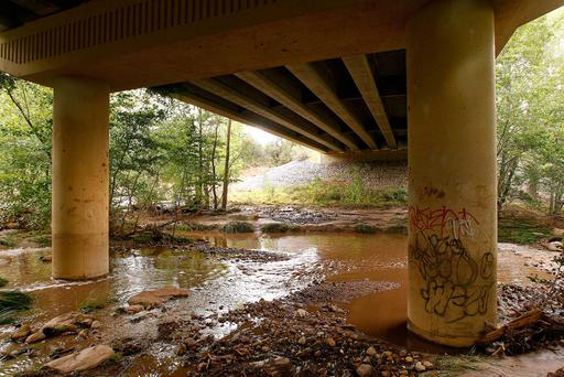 Muddy floodwaters of the East Verde River flow under a bridge were at least one victim of a flash flood was found during a search and rescue operation by the Gila County Sheriff's Office on Sunday, July 16, 2017, in Payson, Ariz. (AP Photo/Ralph Freso)