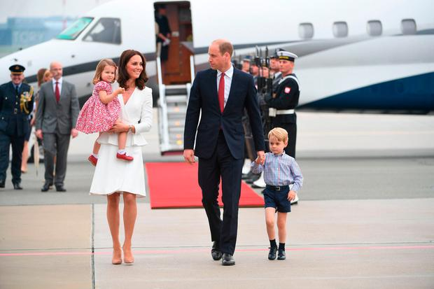 Britain's Prince William, Duke of Cambridge (R) and his wife Kate, Duchess of Cambridge (L) with their children Prince George and Princess Charlotte arrive at the airport in Warsaw, Poland, on July 17, 2017