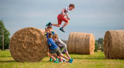 Andrew Power (9) having fun with his friends on bales of hay in North County Dublin yesterday. Photo: Mark Condren