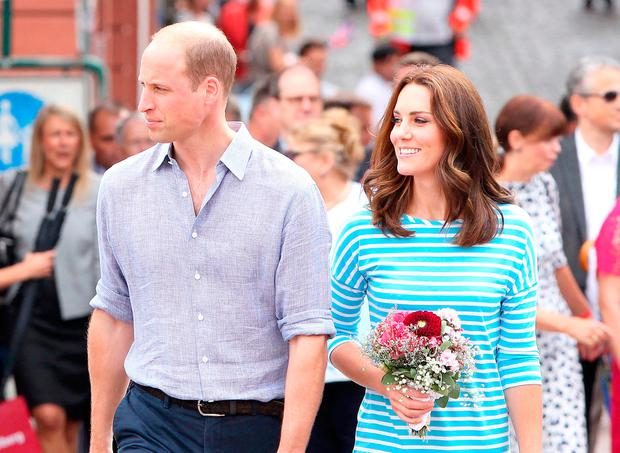 Britain's Prince William, Duke of Cambridge and his wife Kate, the Duchess of Cambridge react as they walk on the Old Bridge in the historic center of Heidelberg, southern Germany on July 20, 2017