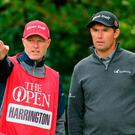 Ireland's Padraig Harrington speaks with his caddie on the 5th