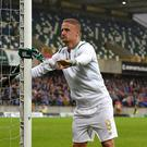 Leigh Griffiths of Celtic ties a Celtic scarf around the goal post after the Champions League second round first leg qualifying game between Linfield and Celtic at Windsor Park on July 14, 2017 in Belfast, Northern Ireland. (Photo by Charles McQuillan/Getty Images)