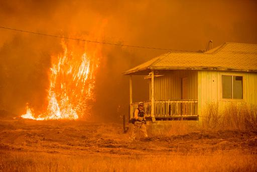 Flames rise behind a vacant house as a firefighter works to halt the Detwiler wildfire near Mariposa, Calif., on Wednesday, July 19, 2017. (AP Photo/Noah Berger)