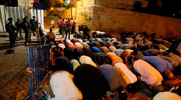Israeli border police stand guard as Palestinians take part in evening prayers outside the Lion's Gate of Jerusalem's Old City July 20, 2017. REUTERS/Ammar Awad