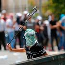 A Palestinian uses a slingshot against Israeli soldiers Photo: AP Photo/Nasser Shiyoukhi