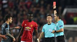 Romanian referee Ovidiu Hategan (R) shows a red card to Manchester United's Ivorian defender Eric Bailly (C), after a clash between players during the UEFA Europa League semi-final, second-leg football match between Manchester United and Celta Vigo at Old Trafford stadium in Manchester, north-west England, on May 11, 2017. / AFP PHOTO / Paul ELLIS