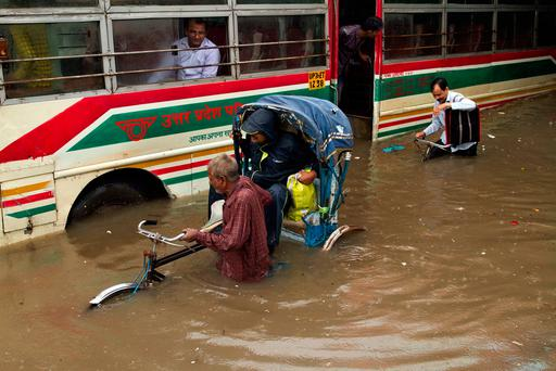 A man from a stranded passenger bus watches an Indian rickshaw puller negotiating through a water logged street following heavy rains in Allahabad, India, Tuesday, July 25, 2017. The monsoon season in India runs from June to September. (AP Photo/Rajesh Kumar Singh)