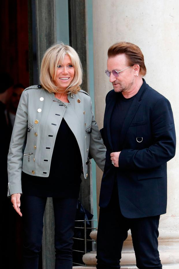 Singer Bono of Irish band U2 and co-founder of ONE organization and Brigitte Macron, wife of the French President, react on the steps at the Elysee Palace in Paris, France, July 24, 2017. REUTERS/Philippe Wojazer