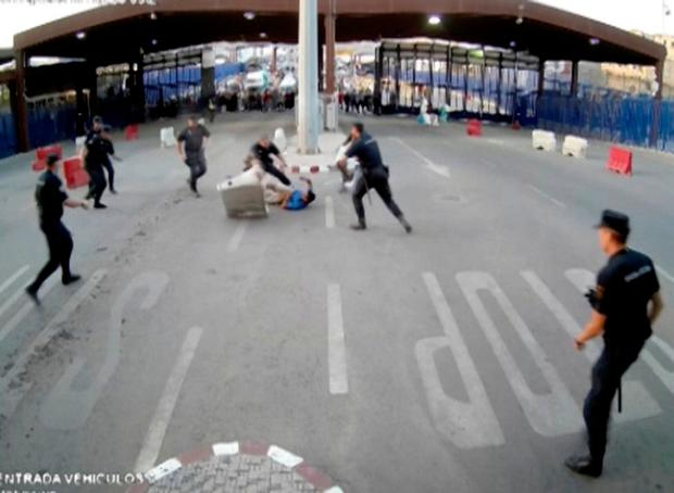Spanish police officers stop a man on the Beni Enzar border crossing between Morocco and the Spanish enclave of Melilla, Spain July 25, 2017 in this still image from a CCTV video. Interior Ministry via REUTERS