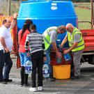 Residents receive water from a dispensing station at Aston Village Drogheda yesterday afternoon. Photo: Colin Keegan, Collins Dublin
