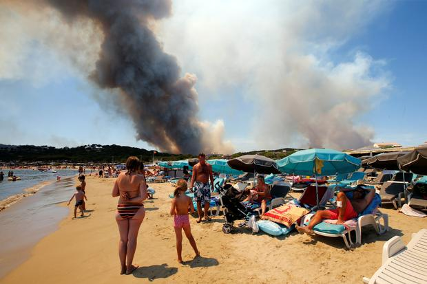 Smoke fills the sky above a burning hillside as tourists relax on the beach in Bormes-les-Mimosas, in the Var department, France, July 26, 2017. REUTERS/Jean-Paul Pelissier