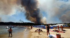 Tourists stand on the beach and watch as smoke fills the sky above a burning hillside in Bormes-les-Mimosas, in the Var department, France, July 26, 2017. REUTERS/Jean-Paul Pelissier