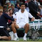 LONDON, ENGLAND - JULY 12: Novak Djokovic of Serbia is given treatment during the Gentlemen's Singles quarter final match against Tomas Berdych of The Czech Republic on day nine of the Wimbledon Lawn Tennis Championships at the All England Lawn Tennis and Croquet Club on July 12, 2017 in London, England. (Photo by Julian Finney/Getty Images)