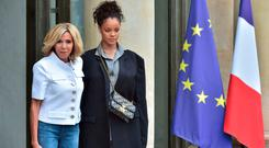 Brigitte Macron (L), wife of the French president, poses with Barbadian musician and Global Ambassador for the Global Partnership for Education Rihanna as she welcomes her at the Elysee Palace in Paris on July 26, 2017. AFP PHOTO / CHRISTOPHE ARCHAMBAULTCHRISTOPHE ARCHAMBAULT/AFP/Getty Images