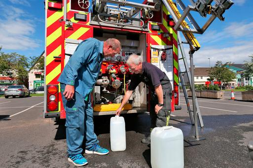 Firefighter Declan Carey fills local man Peter Farrell's water containers in Ashbourne, Co Meath. Photo: Collins
