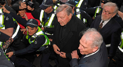 Cardinal George Pell, centre right, is surrounded by police as he arrives at Melbourne Magistrates Court. Photo: AP
