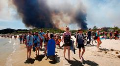 Tourists evacuate the beach as smoke fills the sky above a burning hillside in Bormes-les-Mimosas, France. Photo: REUTERS